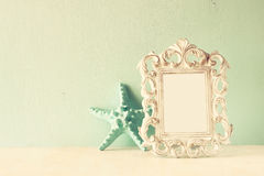 Low key image of vintage antique classical frame and starfish  on wooden table. filtered image Royalty Free Stock Photography