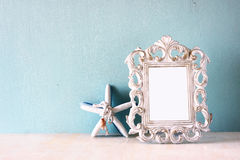 Low key image of vintage antique classical frame and starfish  on wooden table. filtered image Stock Image