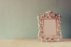 Low key image of vintage antique classical frame on wooden table. filtered image Royalty Free Stock Images