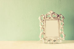 Low key image of vintage antique classical frame on wooden table. filtered image. Low key image of vintage antique classical frame on wooden table. filtered royalty free stock photo