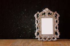 Low key image of vintage antique classical frame on wooden table. filtered image Stock Photography