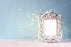 Low key image of vintage antique classical frame and  wooden table and glitter lights background. filtered image Royalty Free Stock Photo