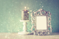 Low key image of vintage antique classical frame and  wooden table and glitter lights background. filtered image. Royalty Free Stock Photography