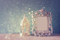 Low key image of vintage antique classical frame and  wooden table and glitter lights background. filtered image Royalty Free Stock Photos