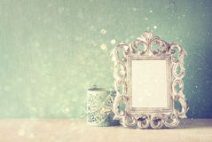 Low key image of vintage antique classical frame and  wooden table and glitter lights background. filtered image. Royalty Free Stock Photo