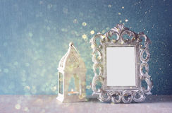 Low key image of vintage antique classical frame and  wooden table and glitter lights background. filtered image Royalty Free Stock Images