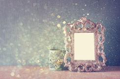 Low key image of vintage antique classical frame and  wooden table and glitter lights background. filtered image. Stock Photos