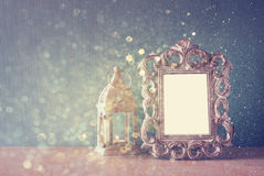 Low key image of vintage antique classical frame and  wooden table and glitter lights background. filtered image Stock Photo