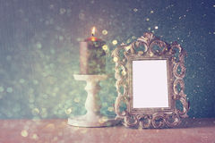 Low key image of vintage antique classical frame and  wooden table and glitter lights background. filtered image. Stock Image