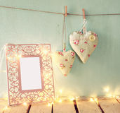 Low key image of vintage pink classical frame, fabric hearts hanging on the rope and lantern with garland lights, on wooden table. Stock Photo