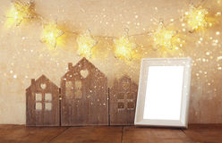 Low key image of vintage wooden house decor, blank frame on wooden table and stars garland. retro filtered with glitter overlay Stock Images