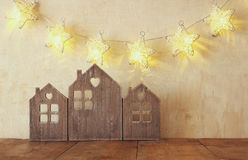 Low key image of vintage wooden house decor on wooden table and stars garland. retro filtered. selective focus Royalty Free Stock Photo