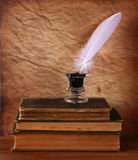 Low key image of white Feather, inkwell and ancient books on old wooden table Royalty Free Stock Photos