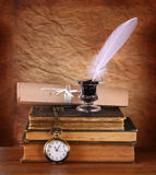 Low key image of white Feather, inkwell and ancient books on old wooden table Stock Images