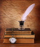Low key image of white Feather, inkwell and ancient books on old wooden table. Royalty Free Stock Photos
