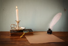 Low key image of white Feather, inkwell, burning Candle and ancient book on wooden table.  filtered image Royalty Free Stock Image