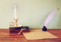 Low key image of white Feather, inkwell, burning Candle and ancient book on wooden table.  filtered image. Royalty Free Stock Photos