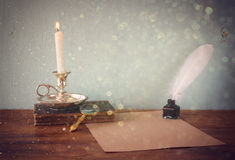 Low key image of white Feather, inkwell, burning Candle and ancient book on wooden table and glitter lights background . filtered Stock Photo