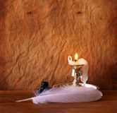 Low key image of white Feather, inkwell and burning candle on a wooden table. Royalty Free Stock Images