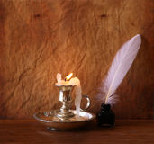 Low key image of white Feather, inkwell and burning candle on a wooden table Royalty Free Stock Image