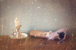 Low key image of white Feather, inkwell, and candle and  glitter lights background on old wooden table. Royalty Free Stock Images