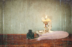 Low key image of white Feather, inkwell, and candle and  glitter lights background on old wooden table Stock Photo