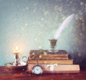Low key image of white Feather, inkwell, old books and candle and  glitter lights background on old wooden table. Royalty Free Stock Image