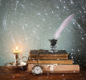Low key image of white Feather, inkwell, old books and candle and  glitter lights background on old wooden table Royalty Free Stock Images
