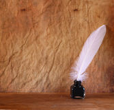 Low key image of white Feather and inkwell on old wooden table Stock Image