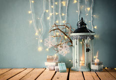 Low key image of white wooden vintage lantern with burning candle christmas gifts and tree branches on wooden table. retro filtere Royalty Free Stock Images