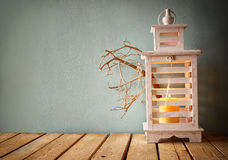 Low key image of white wooden vintage lantern with burning candle and tree branches on wooden table. retro filtered image Stock Photo