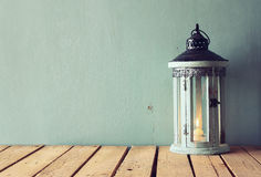 Low key image of white wooden vintage lantern with burning candle and tree branches on wooden table. retro filtered image Stock Photos