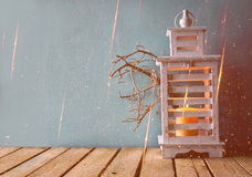 Low key image of white wooden vintage lantern with burning candle and tree branches on wooden table. retro filtered image with gli Royalty Free Stock Image