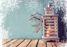 Low key image of white wooden vintage lantern with burning candle and tree branches on wooden table. retro filtered image with sno Royalty Free Stock Image