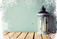 Low key image of white wooden vintage lantern with burning candle and tree branches on wooden table. retro filtered image with sno Royalty Free Stock Photography