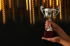 Low key image of a woman holding a trophy cup over dark background. Low key image of a woman holding a trophy cup over dark background royalty free stock photos