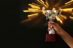 Low key image of a woman holding a trophy cup over dark background. Low key image of a woman holding a trophy cup over dark background stock image