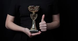 Low key image of a woman holding a trophy cup over dark background