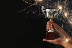 Low key image of a woman holding a trophy cup over dark background. Low key image of a woman holding a trophy cup over dark background royalty free stock images