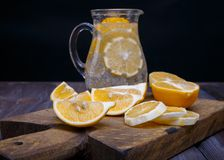 Low key lemons. Some sliced lemons on a wooden cutting board and pitcher of water Royalty Free Stock Photo