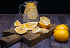 Low key lemons. Some sliced lemons on a wooden cutting board and pitcher of water Stock Photo