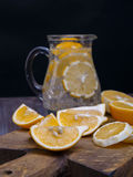 Low key lemons. Some sliced lemons on a wooden cutting board and pitcher of water Royalty Free Stock Image