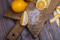 Low key lemons. Some sliced lemons on a wooden cutting board and sea salt Royalty Free Stock Photo