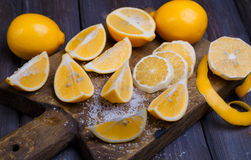 Low key lemons. Some sliced lemons on a wooden cutting board and sea salt Royalty Free Stock Images