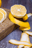 Low key lemons. Some sliced lemons on a wooden cutting board and sea salt Stock Image