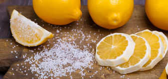 Low key lemons. Some sliced lemons on a wooden cutting board and sea salt Stock Photo