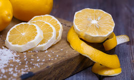 Low key lemons. Some sliced lemons on a wooden cutting board and sea salt Royalty Free Stock Photography