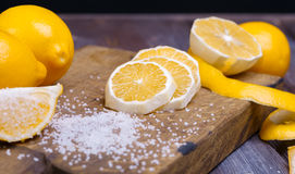 Low key lemons. Some sliced lemons on a wooden cutting board and sea salt Stock Images