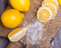 Low key lemons. Some sliced lemons on a wooden cutting board and sea salt Stock Photos