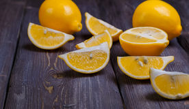 Low key lemons. Some sliced lemons on a wooden table Stock Photo